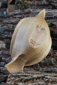 This view of the underside shows the carving beneath the tail and the egg-shaped bottom surface of the bowl.