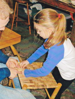 Emma helping to weave a hickory bark stool seat.